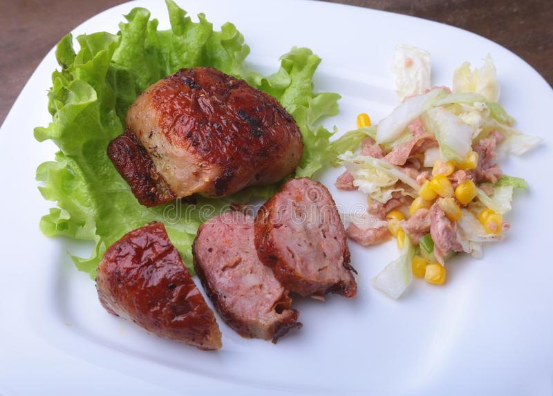 Marinated roaste chicken breasts cooked on BBQ and served with fresh salad on white plate, close-up. stock image