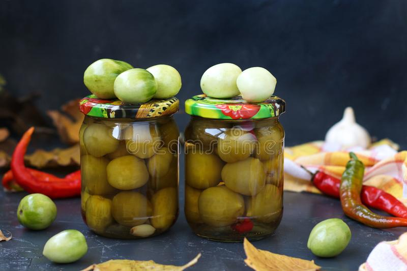 Marinated spicy green tomatoes are located in banks against a dark background. Preparation for the winter royalty free stock image