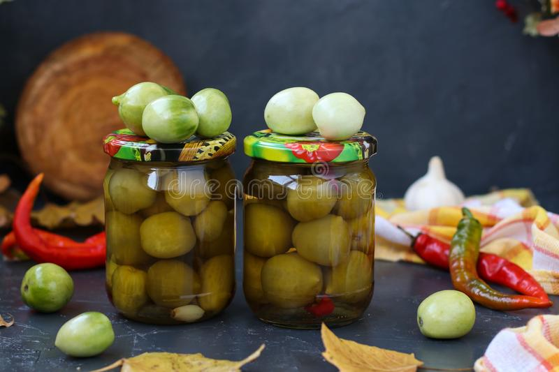 Marinated spicy green tomatoes are located in banks against a dark background. Preparation for the winter stock photos