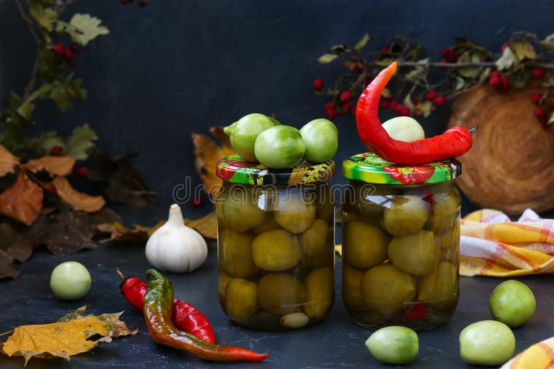 Marinated spicy green tomatoes are located in banks against a dark background. Preparation for the winter stock image