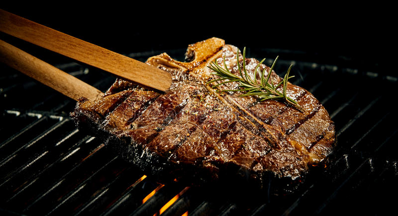 Marinated spicy lean t-bone steak on a BBQ stock image
