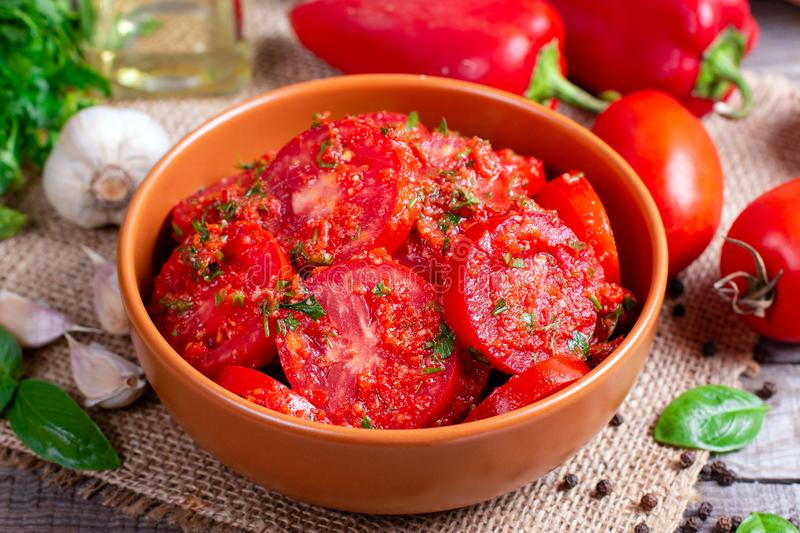 Marinated tomatoes  in a bowl. Marinated tomatoes. Tomatoes in a bowl with herbs and garlic stock photography