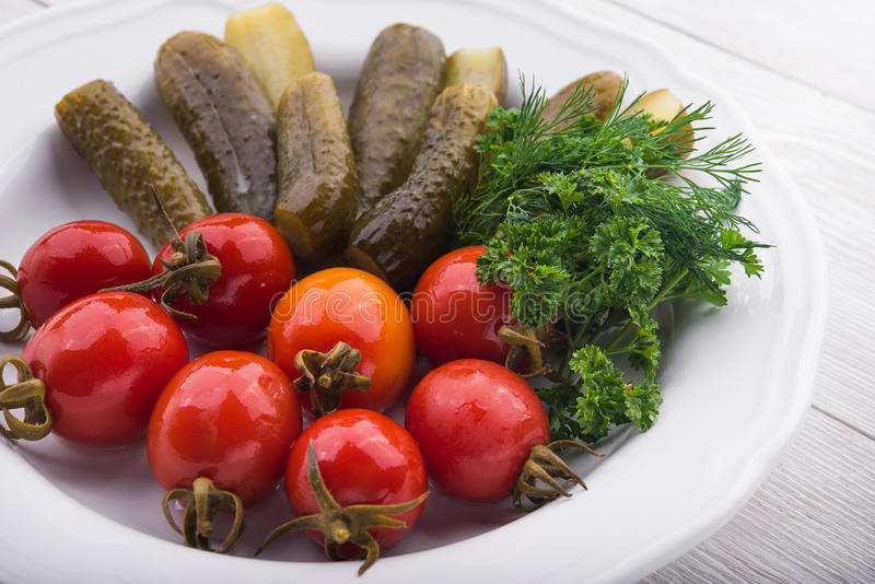 Marinated tomatoes and cucumbers. On a white plate stock photos