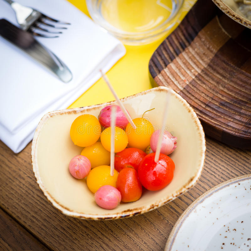 Marinated tomatoes and eatberries. Snack of marinated tomatoes and eatberries in the restaurant stock images