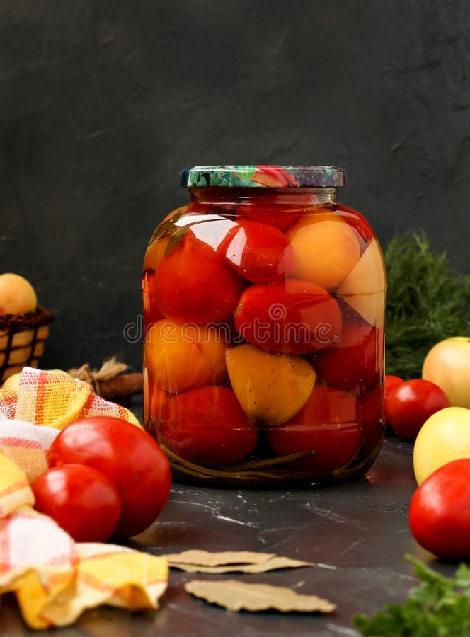 Marinated tomatoes in jar are located on a dark background. Harvesting for the winter stock image