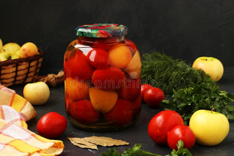 Marinated tomatoes in jar are located on a dark background. Harvesting for the winter stock photography