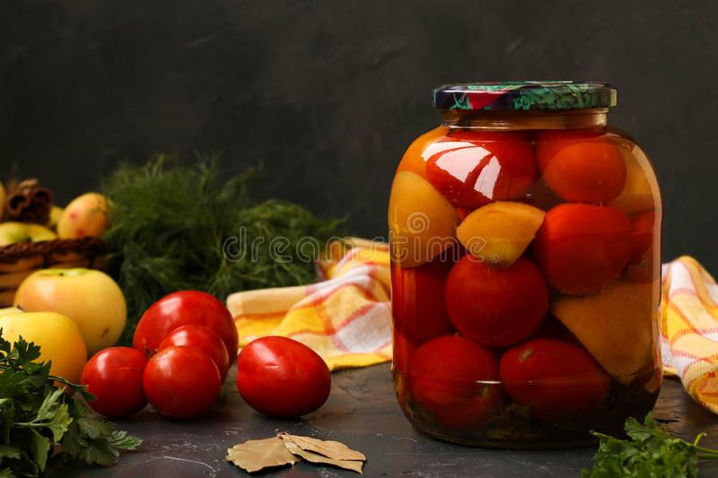 Marinated tomatoes in jar are located on a dark background. Harvesting for the winter royalty free stock photography