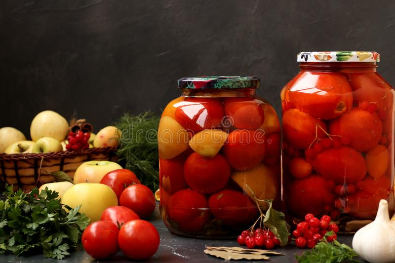 Marinated tomatoes in jars are located on a dark background. Harvesting for the winter royalty free stock image