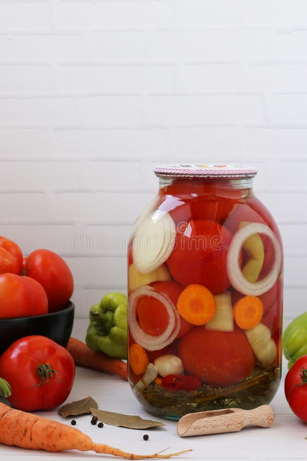 Marinated tomatoes with onions, peppers and carrots in can are located on a white background. Vertical photo. Harvest for the winter stock photos