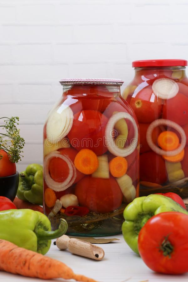 Marinated tomatoes with onions, peppers and carrots in can are located on a white background. Marinated tomatoes with onions, peppers and carrots in cans are stock images