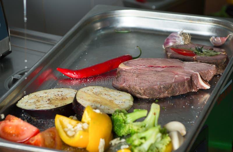 Marinating мясо и зажаренные овощи на подносе стоковые фото