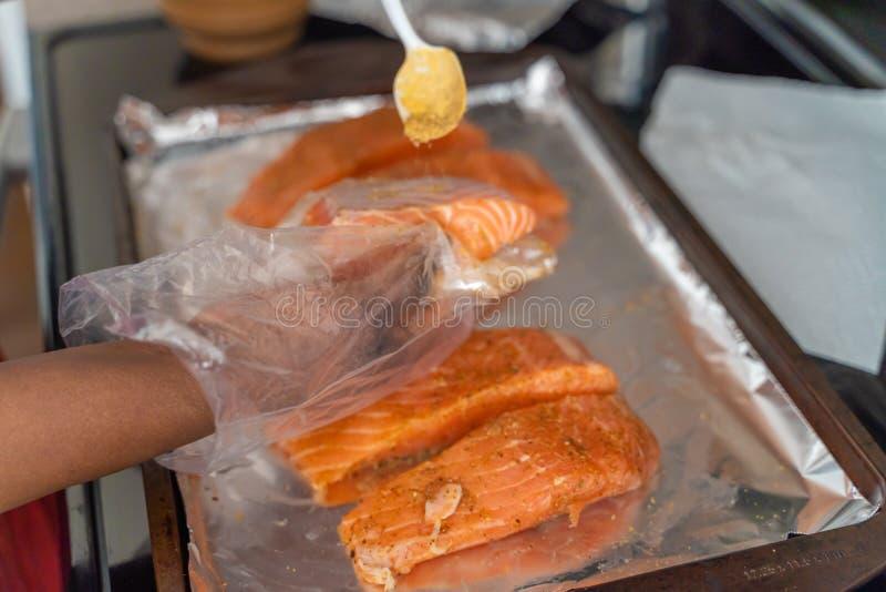 Marination des biftecks saumonés organiques frais avant de griller images stock