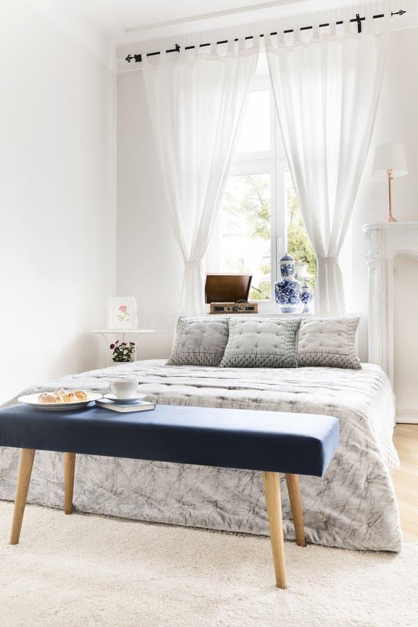 Marinblå bänk med bok- och frukostanseende av konungen-siz arkivfoton
