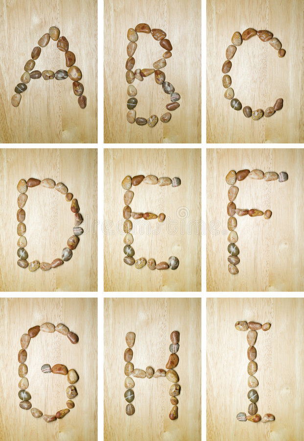 Marine alphabet A-I. Summertime english alphabet made of marine stones. background is rubber tree (seringa stock image