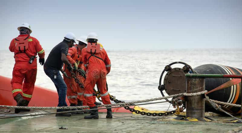 Marine crew doing hose connection operation royalty free stock image