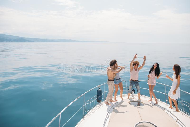 Marine cruise and vacation - youngsters with champagne glasses on boat or yacht stock images