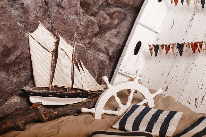 Marine decorations. Ship and wheel in sand. royalty free stock photography