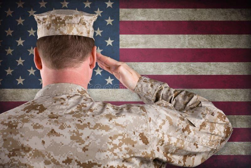 Marine, die eine amerikanische Flagge begrüßt stockfotos