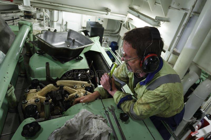Marine Engineer, die einen Dieselmotor instandhält stockfotos