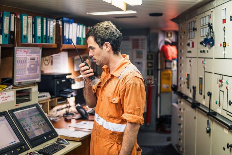 Marine Engineer som arbetar på radiokommunikation på motorkontrollrum royaltyfri foto