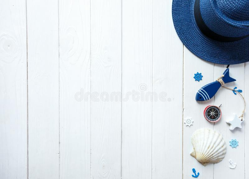 Marine items on wooden background. Sea objects: straw hat, swimsuit, fish, shells . flat lay, copy space. vacation and travel royalty free stock photo