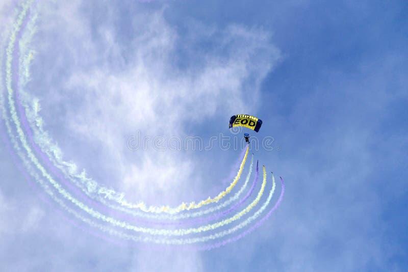 Marine parachuter, das mit bunten Rauchströmen skywriting ist lizenzfreie stockbilder