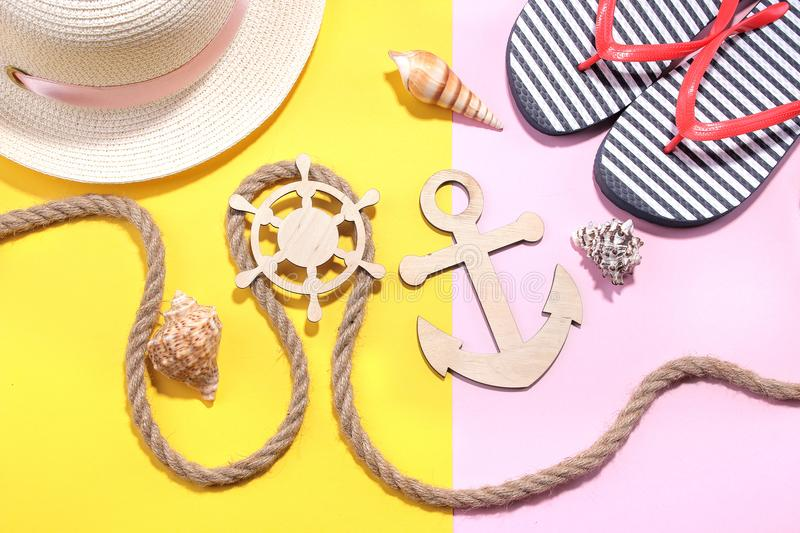 Marine paraphernalia and beach accessories. Wooden steering wheel and an anchor with a rope on a bright pink and yellow background stock photo