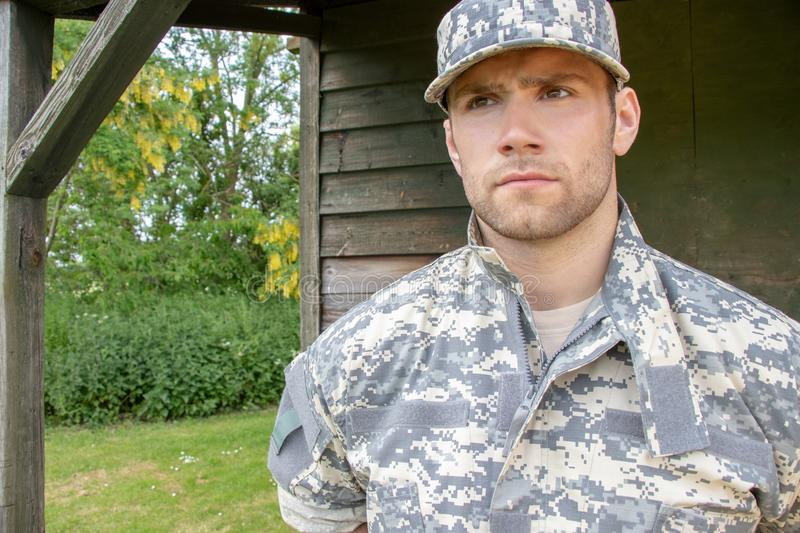 Marine, soldier in his army fatigues stands to attention at military base. Muscular military man in army fatigues and cap stands to attention while guarding army royalty free stock photos