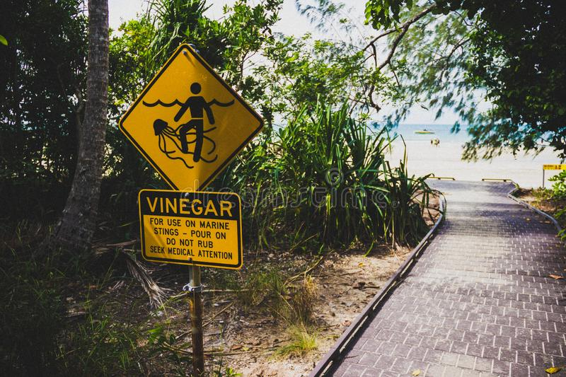 Marine Stinger Sign and Vinegar bottle. In case you get stung by them. Australia, symbol, wild, burn, nature, tentacle, venom, caution, blue, safety, drawing royalty free stock photos