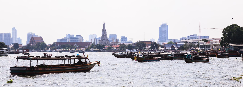 Marinenahverkehr des thailändischen Flussufers in Chao Phraya River mit Wat Arun Temple des Dämmerungshintergrundes, Bangkok, Tha lizenzfreie stockbilder