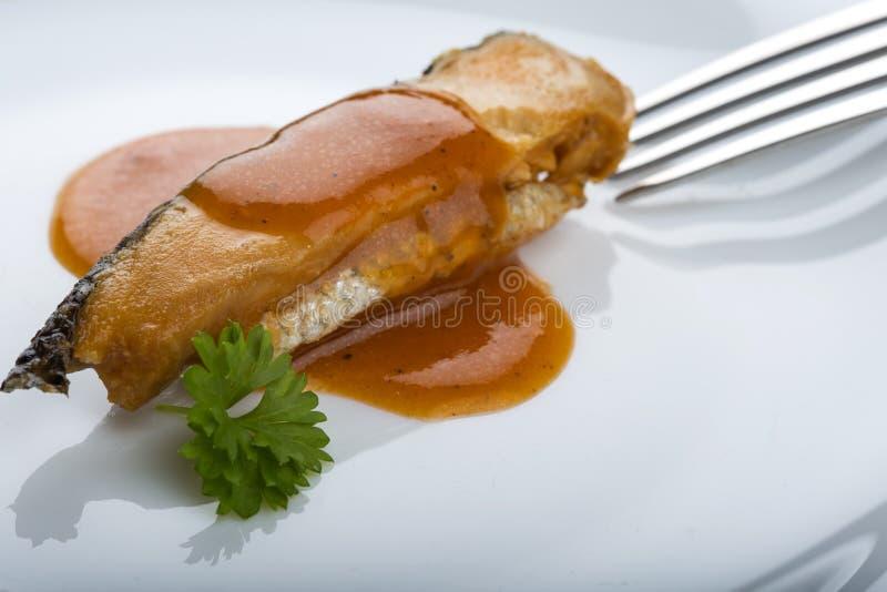Marinerad sillfisk i tomatsås på plattan med persilja och royaltyfri fotografi