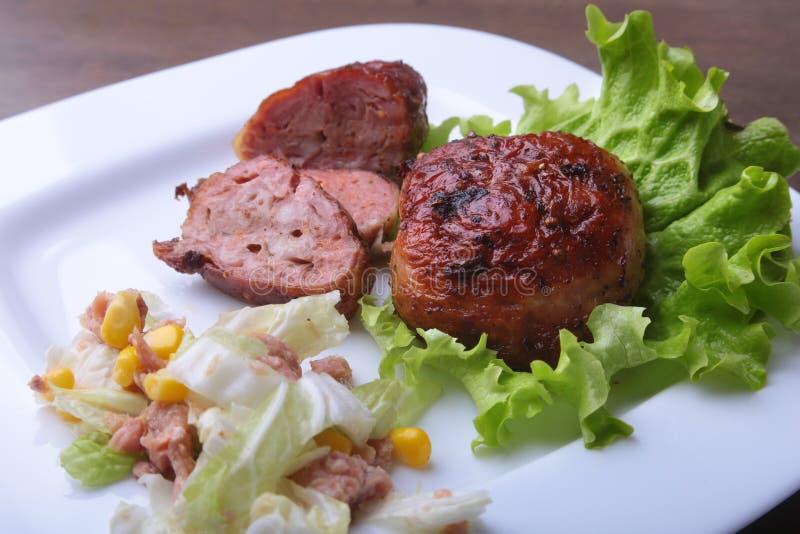 Marinerade fega bröst för roaste som lagas mat på BBQ och tjänas som med ny sallad på den vita plattan, närbild royaltyfria foton