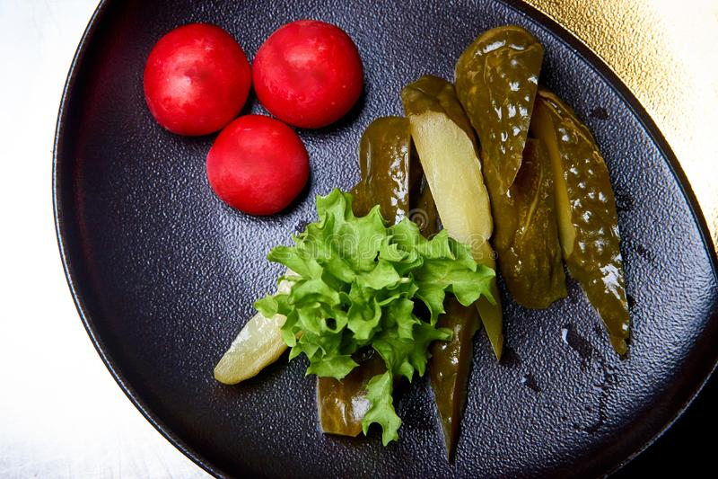 Marinerade gurkor, ny sallad och rädisa på en plattanärbild arkivbilder