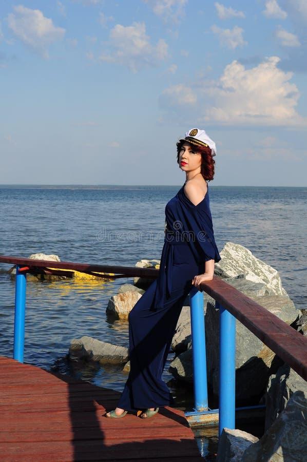 Marinero de la chica joven que camina en el embarcadero y que espera su nave en el verano fotografía de archivo