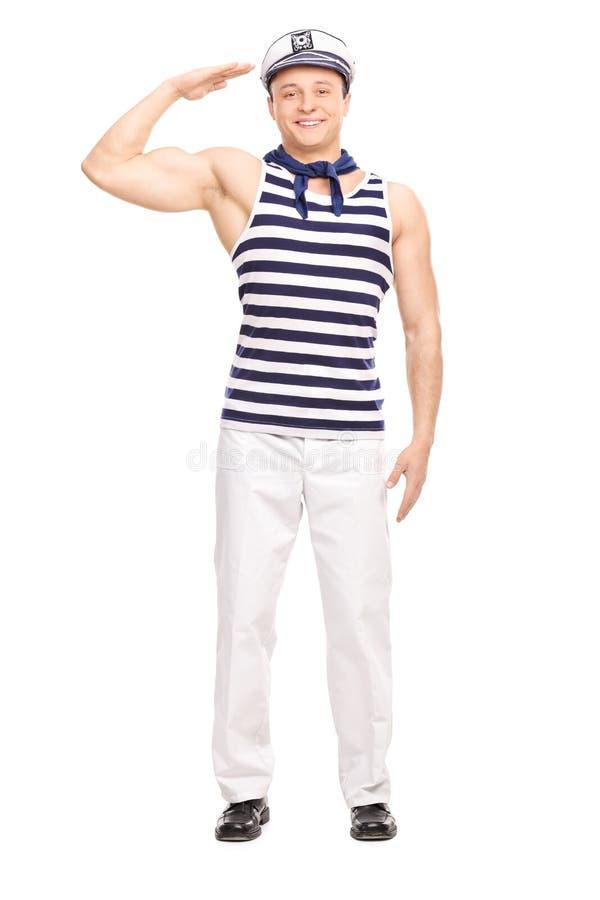 Marinero de sexo masculino joven que se coloca recto y el saludar fotografía de archivo libre de regalías