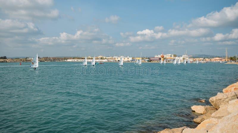 Marineros internacionales en los barcos de navegación del viento que entran en el puerto deportivo de Vilamoura, Portugal fotos de archivo libres de regalías