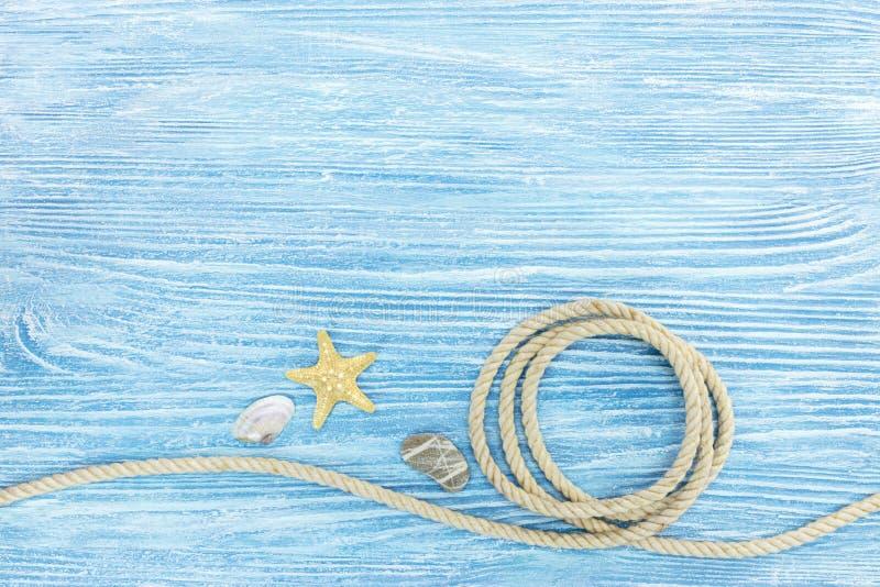 Marinesteine und Muscheln, Seil auf gemalten blauen hölzernen Brettern stockfoto