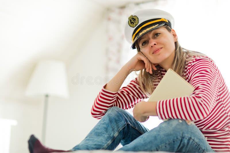 Marinheiro da jovem mulher no tampão e no livro do capitão imagens de stock