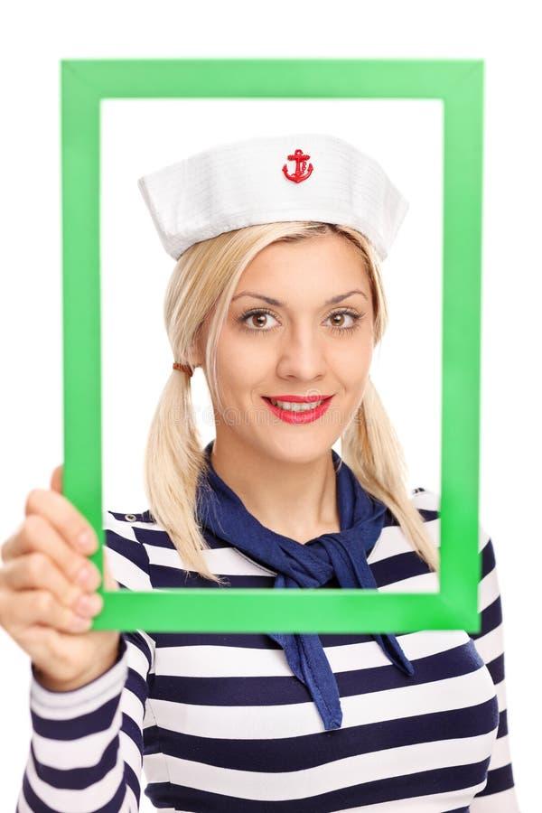 Marinheiro fêmea novo que guarda uma moldura para retrato verde fotos de stock royalty free