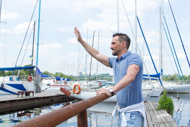 Marinheiro masculino que acena acima no cais e no sorriso O 'yachtsman' dá o comando amarrar à mão na doca Boas vindas do homem q imagens de stock