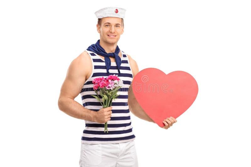 Marinheiro que guarda flores e um coração fotografia de stock
