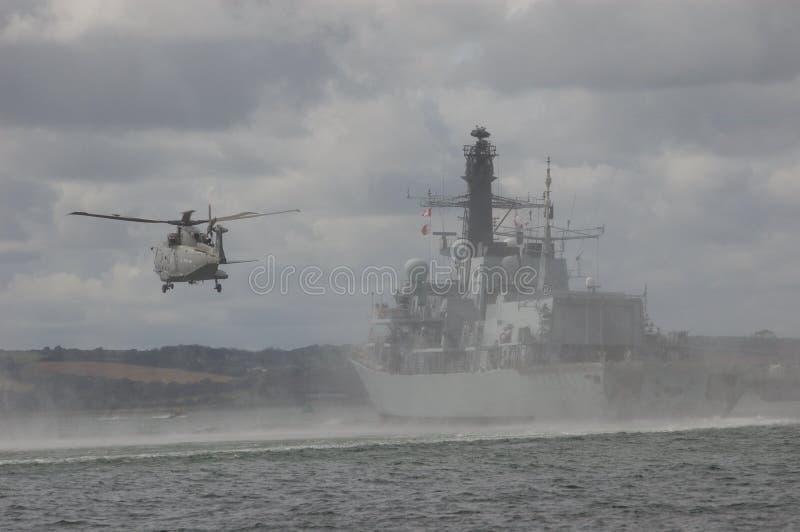 Marinhelikopter och krigsskepp fotografering för bildbyråer