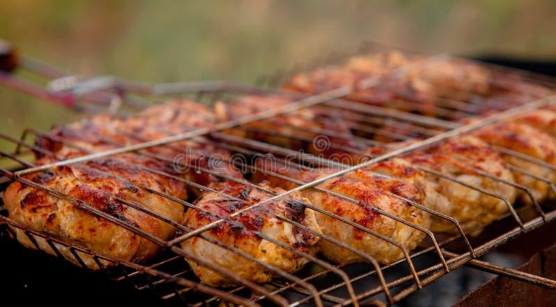 Marinierte Hühnerbeine auf dem Grill im Rauche Ein Picknick, geschmackvolles Lebensmittel BBQ stockfotografie