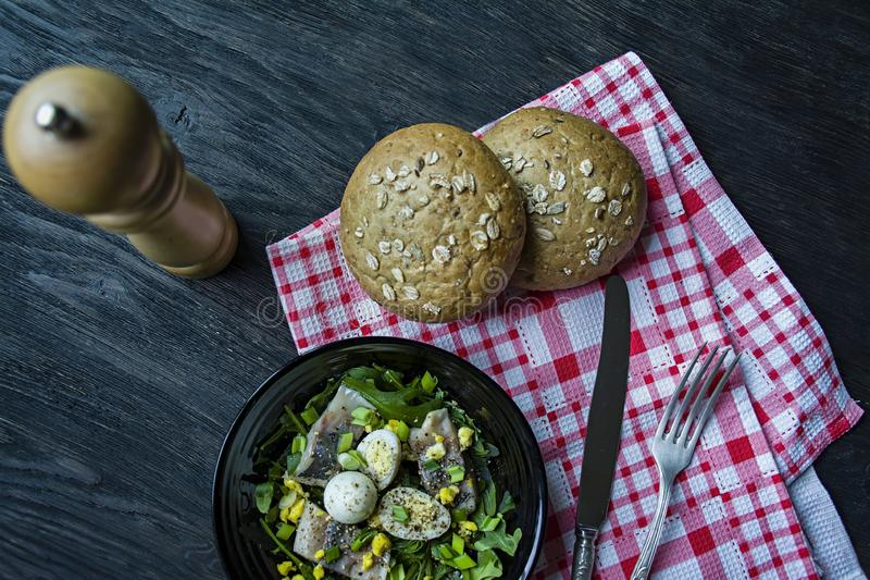 Marinierte Heringe mit Arugula, Zwiebeln, gekochte Wachteleier und Zitronensaft und Oliven?l K?stlicher Salat Richtige Nahrung du lizenzfreie stockfotos