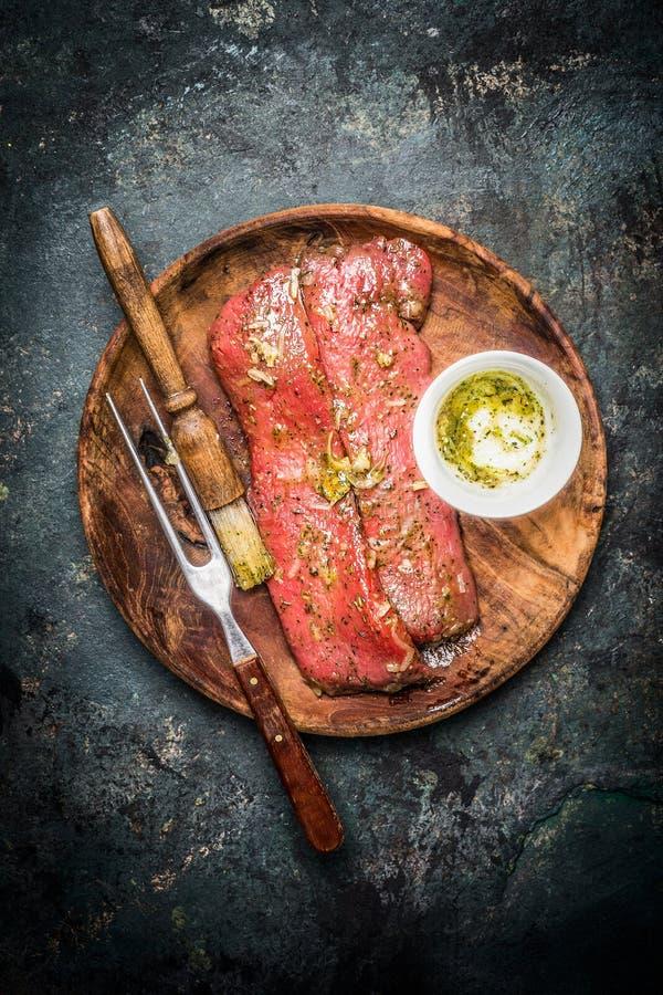 Marinierte Lammleiste für das Kochen oder BBQ-Grill mit Bürste und Fleisch gabeln in der hölzernen Platte, Draufsicht lizenzfreie stockbilder