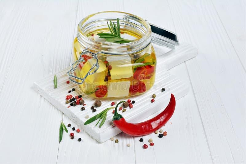 Mariniertes Feta mit Olivenöl und Gewürz des Pfeffers und des Rosmarins des roten Paprikas im Glasgefäß stockfoto