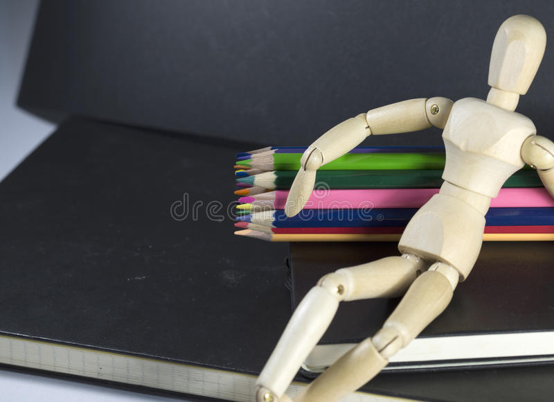 Marioneta de madera que se sienta en Sketchbook imagen de archivo