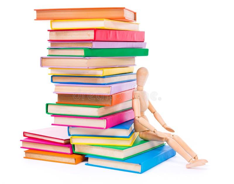 Marioneta simulada de madera que se sienta en los libros imagenes de archivo
