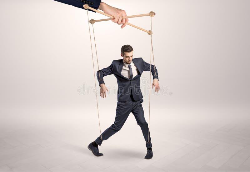 Marionettengeschäftsmann verbleit durch eine riesige Hand stockbilder