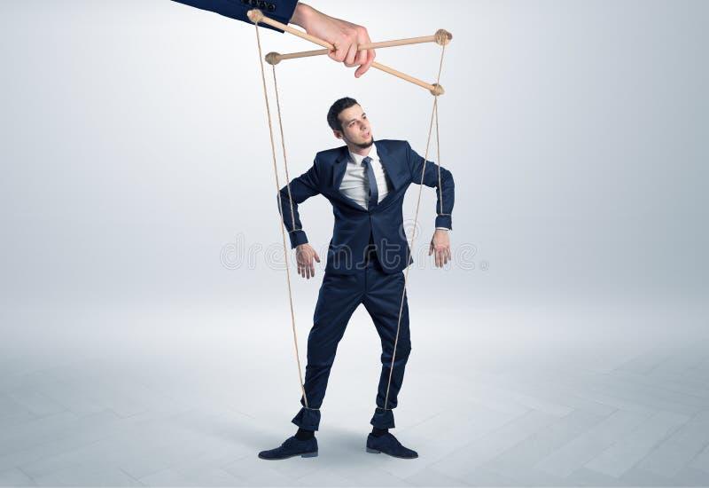 Marionettengeschäftsmann verbleit durch eine riesige Hand lizenzfreies stockfoto